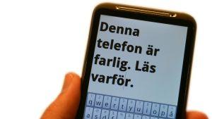 smarttelefon med texten: denna telefon är farlig. läs varför. på skärmen