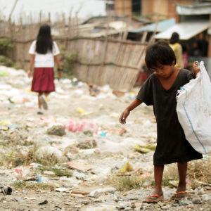 Pojke på Filippinerna plockar material för återvinning i slumområdet utanför Manila.