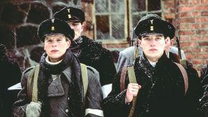 Närbild på unga soldater som står uppställda på rad utomhus i snöfall.