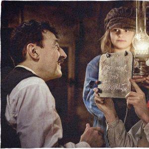 Albert, unga Louise och Edouard tittar på varandra i fotogenlampans sken.