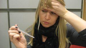 En kvinna håller sig för pannan och tittar på en febertermometer.