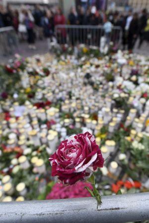 En rosavit ros i görgrunden framför ett hav av ljus och blommor som sörjande människor har placerat på Salutorget i Åbo.