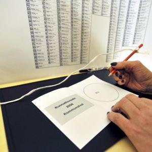 En väljare fyller i valsedeln i kommunalvalet år 2008
