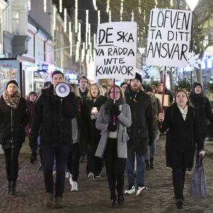 Demonstrationståg med megafon och plakat på en gata.