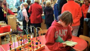 Nuori poika istuu pöydällä ja lukee kirjaa. Hänen takanaan on paljon ihmisiä selin.