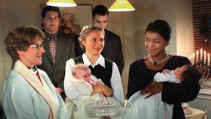 Kotikatu-sarjan näyttelijöitä ristiäisissä. Mirjalla ja Mariamilla on sylissään vauvat.