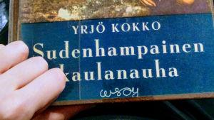 Lukuneuvos-blogin kirjoittaja pitelee kädessään Yrjö Kokon Sudenhampainen kaulanauha -kirjaa.