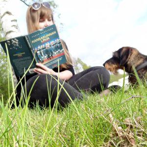 1001 elämää ja yksi pieni elämä -blogin kirjoittaja lukee Paavo Haavikkoa puistossa.