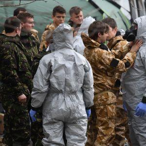 Brittisk militär klädde på sig skyddsdräkter på söndagen då de förberedde sig för att flytta bort bilar från en parkering i Salisbury.