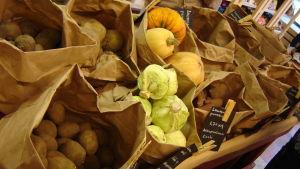 Olika grönsaker i papperspåsar på en matmarknad.