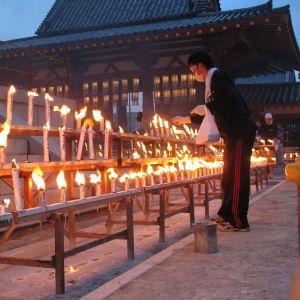 Kuolleiden sielujen muistoksi sytytettyjä kynttilölöitä japanilaistemppelin pihalla.