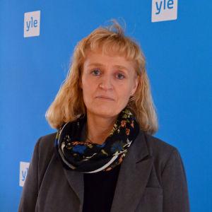 Marianne Pekola-Sjöblom står framför en blåvägg med Yle-logon.
