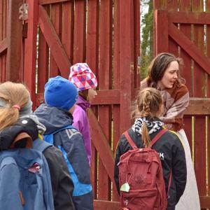 Pigan (Helena Laxén) öppnar en grind för skolbarn som deltar i ett skådespel.