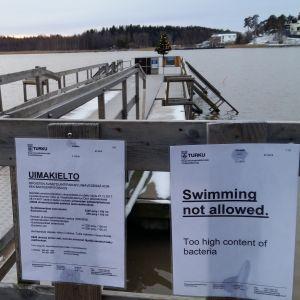 Skylt på finska och engelska om badförbud på grund av för höga halter enterokocker i vattnet vid Ispois vinterbad.