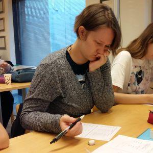 Jasmine Öjbro och tre andra utländska kvinnor läser finska på en kurs.