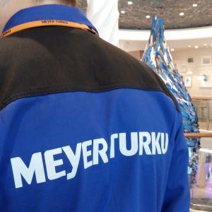 Ryggen med texten Meyer Turku på en arbetare ombord på kryssningsfartyget Mein Schiff 1, som byggdes vid Åbovarvet. I bakgrunden en stor lampa med fiskamotiv.