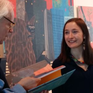 Ulf Stark och Linda Bondestam samtalar och tittar på en bok.