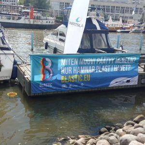 En havssoptunna finns i Åbo gästhamn, med en stor banderoll invid: Hur hamnar plast i vattnet?