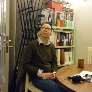 Mio Lindman sitter vid runt bord med bokhylla och spegel i bakgrunden.