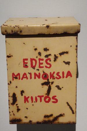 """Kari Cavéns konstverk som föreställer en rostig brevlåda med texten """"Edes mainoksia, kiitos"""" från år 2011."""