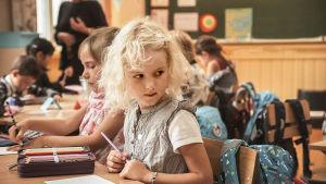 En flicka i sin pulpet i årskurs 1.