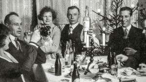 Svartvit bild av julfirande och sex personer som sitter runt ett bord.