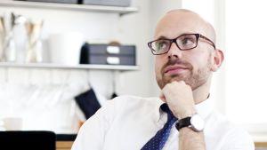 Oscar Ohlis, en av vegas sommarpratare 2014 blickar bakåt, ser fundersam ut, klädd i kragskjorta och slips i ett vitt rum