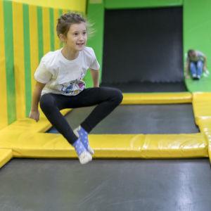 En flicka hoppar på en trampolin i en aktivitetshall.