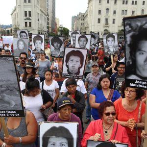 Många demonstranter i Lima bar på porträtt på människor som dödades i massakrer beordrade av Fujimori.
