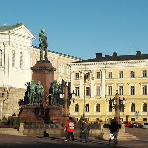 Turister som tittar på statyn av Alexander II på senatstorget