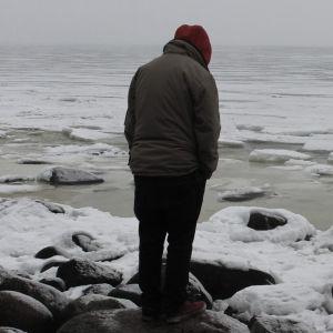 En person tittar ut över ett fruset hav.