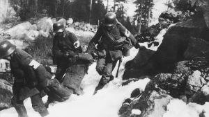 Tyska soldater bär en skadad rödgardist bort från klipporna i Fredriksberg(Böle) i Helsingfors år 1918.