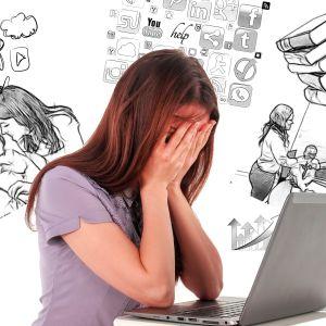 Kvinna vid dator håller händerna för ansiktet