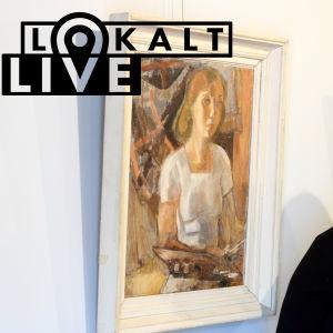 Sari Salo-Kiljo står bredvid ett självporträtt av Tove Jansson.