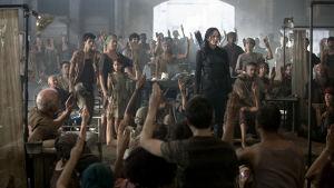 Katniss Everdeen står i en sal med en massa människor runt sig.