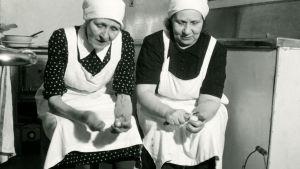 Två kvinnor i vita förkläden och vita huvuddukar sitter och skalar potatis i restaurangköket till Kuopio station.