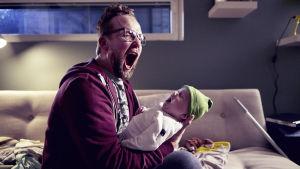 Trött pappa med likaledes gäspande baby.