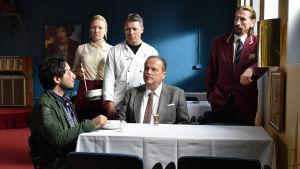 Khaled (Sherwan Haji) sitter vid ett bord och blir serverad soppa, vid bordet sitter även Wikström (Sakari Kuosmanen) och runtom står tre personer och ser Khaled.