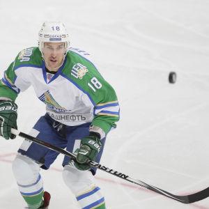 Grön- och vitklädd ishockeyback tar emot studsande puck.
