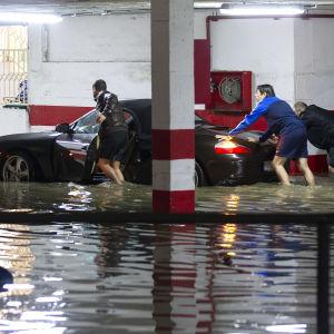 Män skuffar en bil i ett översvämmat parkeringshus.