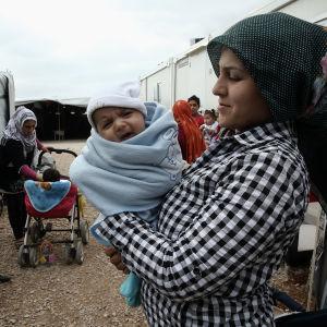 Syriska flyktingar i lägret Ritsona, norr om Aten. I förgrunden en kvinna som håller i ett spädbarn.