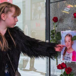 Flicka bredvid ett foto av ett av offren för terrorangreppet på Drottninggatan 2017.