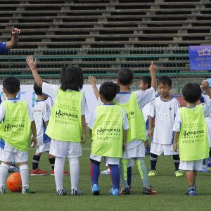 Keisuke Honda tränar småbarn i fotboll.