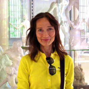 Taiteilija Riitta Nelimarkka Pariisissa kuvanveistäjä Rodinin ateljeetalossa 2010. Veistokset ovat vaaleita ja hämyisiä ja muodostavat värivastakohdan keltaisessa puserossa etualalla olevan taiteilijan kanssa.