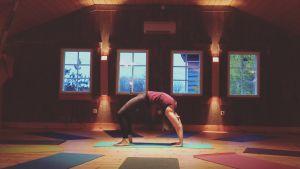 en kvinna som gör en brygga, yogaövning inne i en sal.