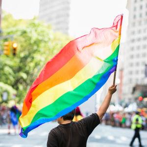 En person i svart t-tröja håller i en regnbågsflagga.