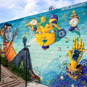 Suuri, värikäs, fantasiamainen seinämaalaus Myyrmäen juna-aseman ulkoseinissä, sinivihreitä hahmoja.