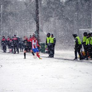 Spelarna försöker löpa efter bollen på den hala planen.