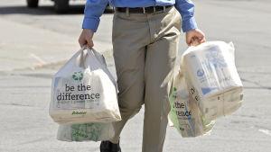 En man bär på plastkassar.
