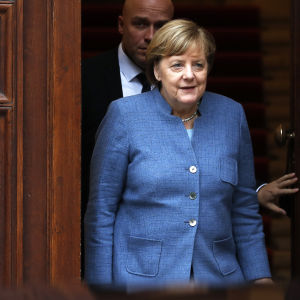 Angela Merkel går ut genom dörren efter en dag av regeringssondering.